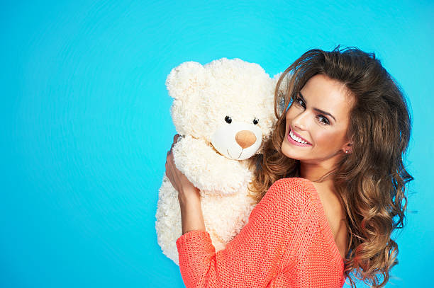 Lovely smiling young woman with big soft teddy bear stock photo
