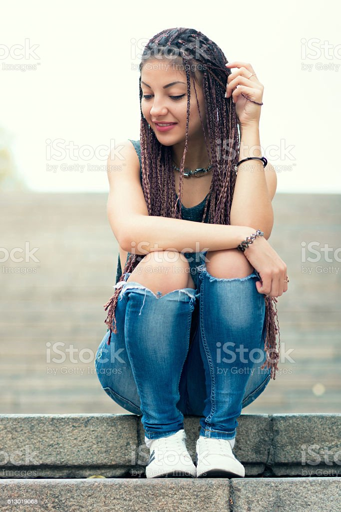 Lovely stylish woman sitting on stairs and smile stock photo