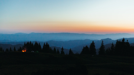 Panoramic view of the summer sunset above the blue mountain layered peaks, pine forest and the campsite with fireplace