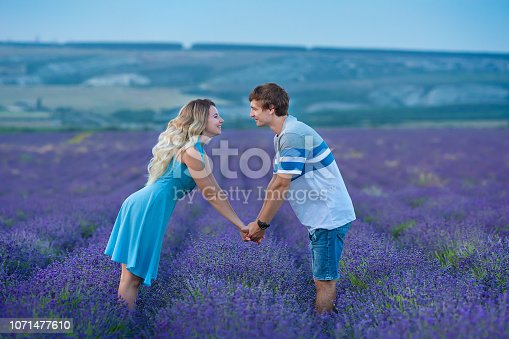 istock Lovely teen couple wearing blue clothes holding each other by hands while standing on a field of lavender flowers. Tender scene of love between two genders. 1071477610