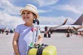 Young and beautiful toddler girl, boarding a plane on a airport.