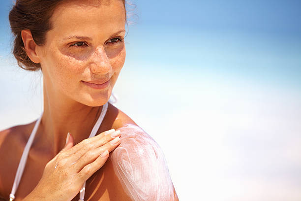 Lovely woman applying lotion Closeup of lovely young woman applying sunscreen lotion on body suntan lotion stock pictures, royalty-free photos & images
