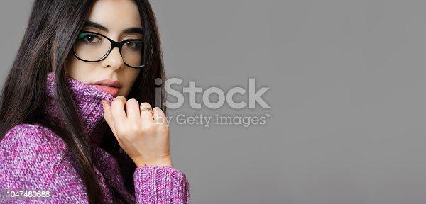 Side view of sensual female in warm knitted sweater and stylish glasses looking at camera while standing on gray background