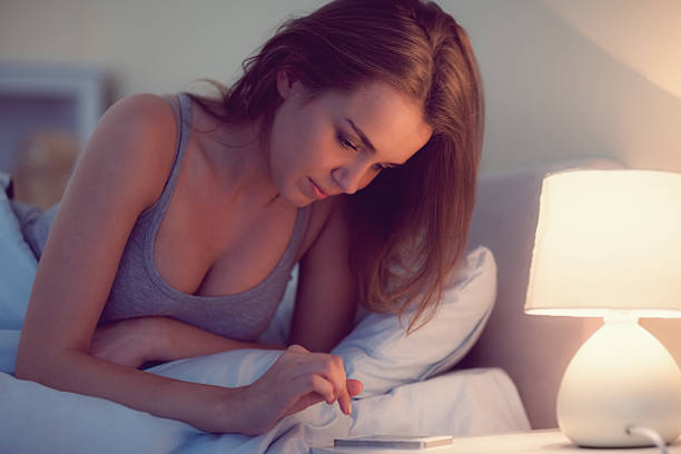 schöne frau liegen im bett mit ihrem smartphone - nachttischleuchte touch stock-fotos und bilder