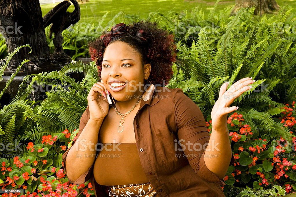Lovely woman on the phone in flower garden royalty-free stock photo