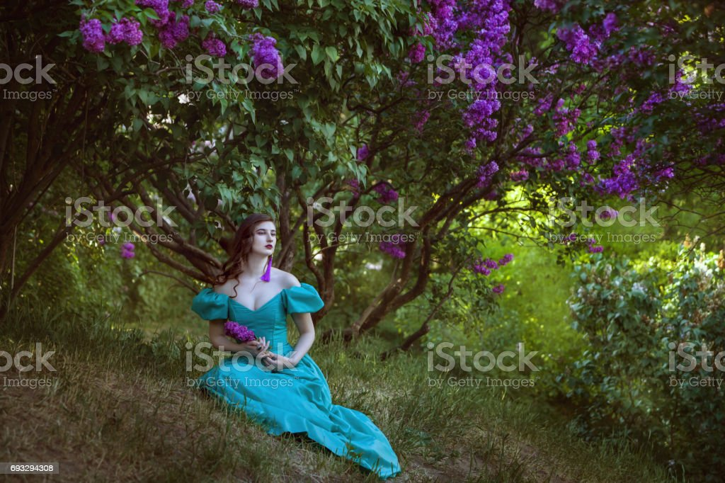Lovely woman under a bush of lilac. stock photo