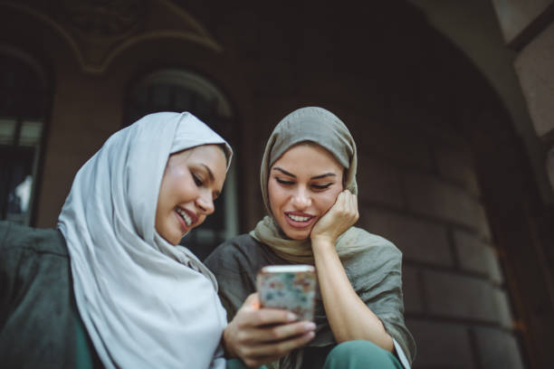lovely woman wearing hijab looking at a mobile phone - скромная одежда стоковые фото и изображения