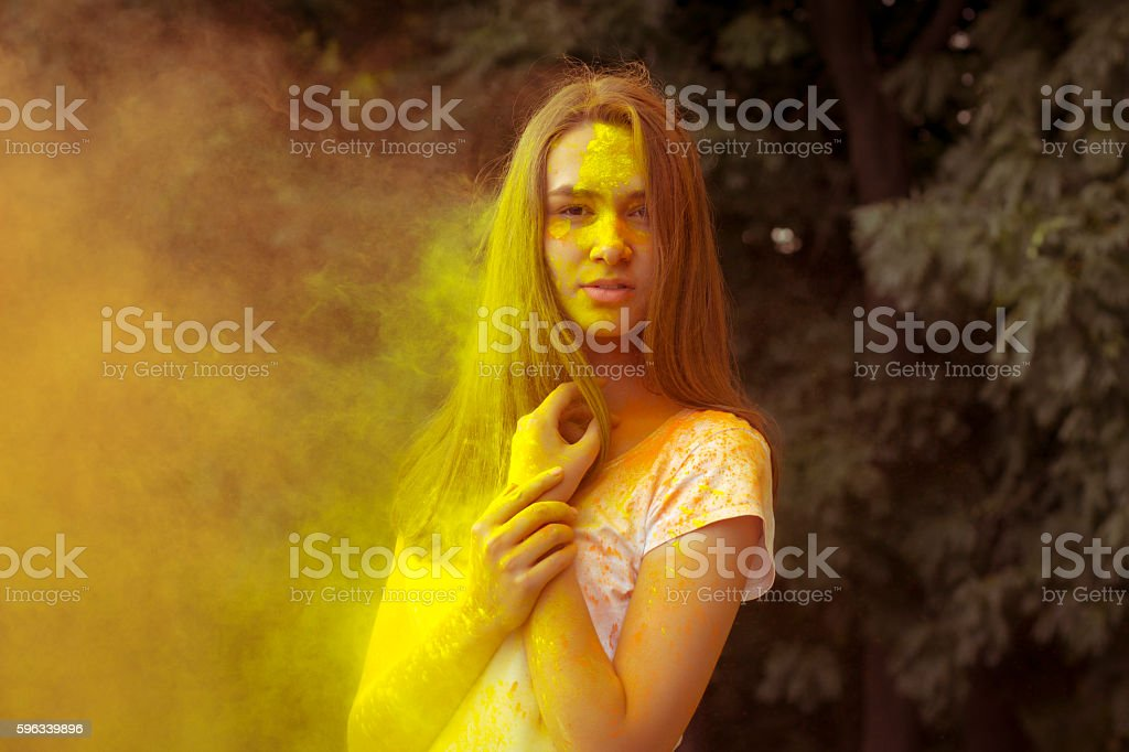 Lovely woman with colorful powder blowing in her face Lizenzfreies stock-foto