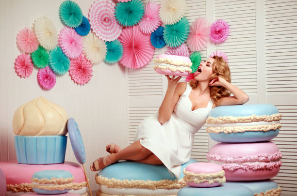 lovely woman with huge marshmallow and cake sweets concept studio - big cake stock photos and pictures