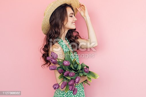 Lovely woman with purple tulips bunch