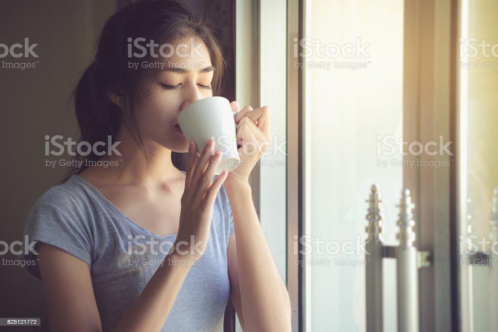 Schöne Frauen sind gerne am Wochenende mit einem hellen Sonnenschein am Fenster Kaffeetrinken. Life-Style-Konzeption – Foto