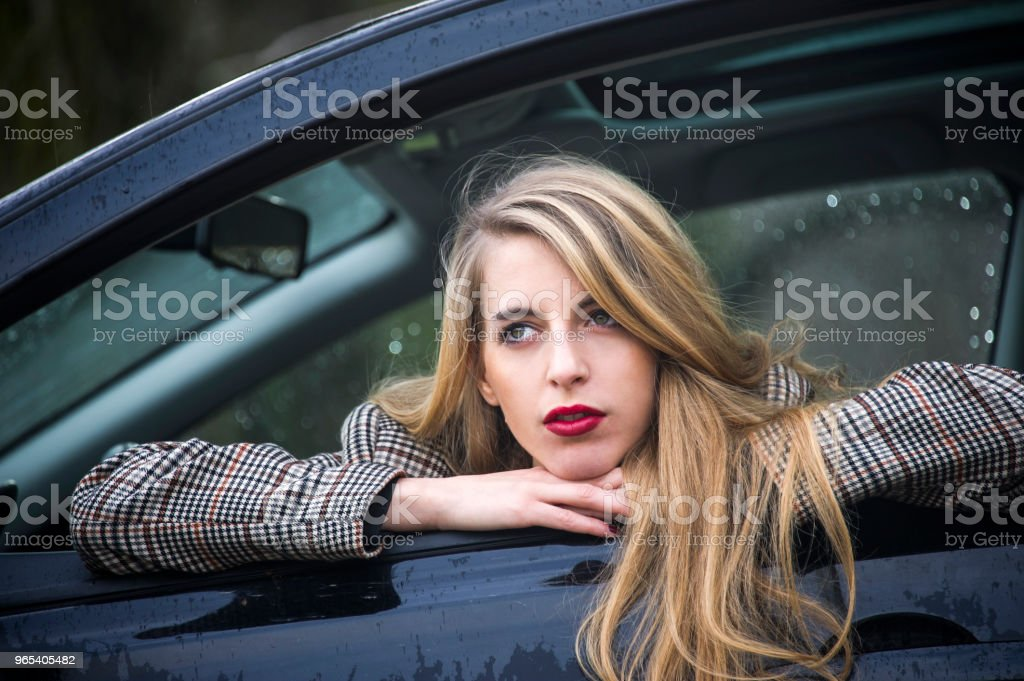 Lovely young blonde woman is leaning out of the window of her car. royalty-free stock photo