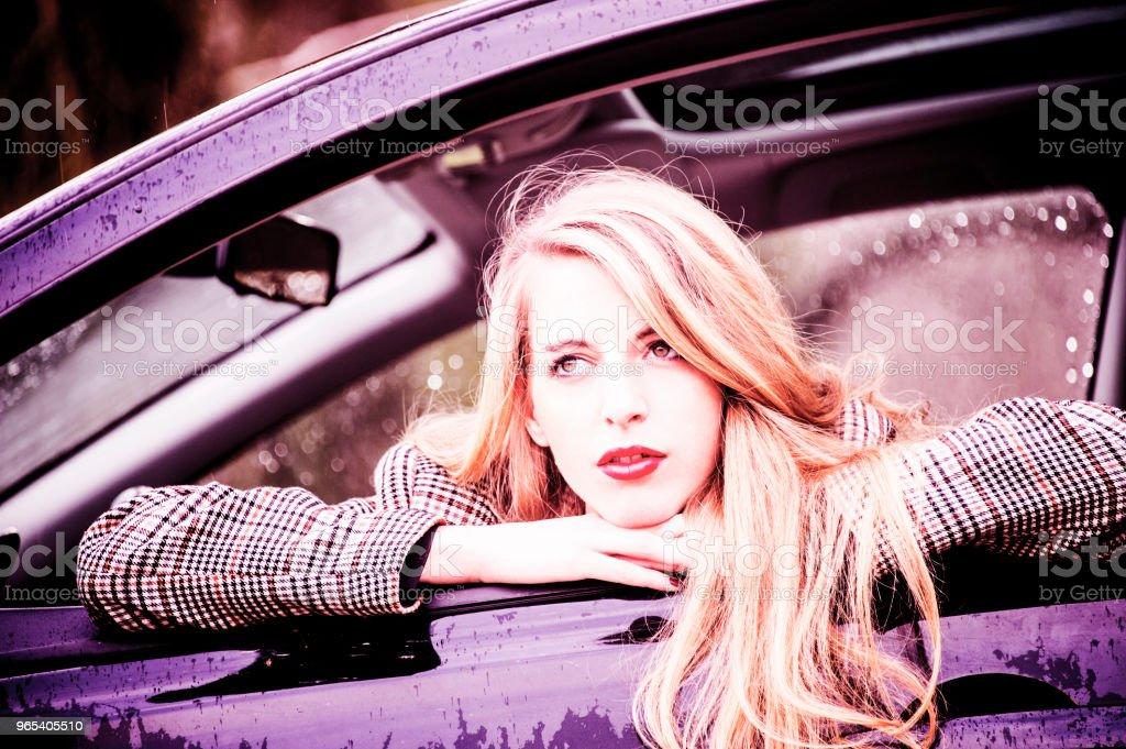 Schöne junge blonde Frau lehnt sich aus dem Fenster ihres Autos. - Lizenzfrei Astronomie Stock-Foto