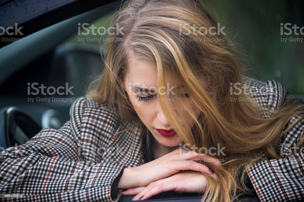Lovely young blonde woman is leaning out of the window of her car. zbiór zdjęć royalty-free