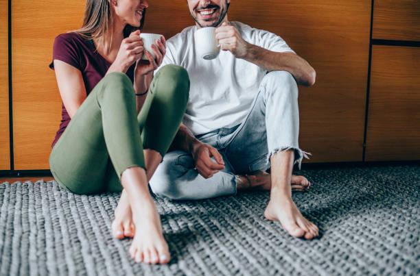 encantadora pareja joven bebiendo café en casa. - happy couple sharing a cup of coffee fotografías e imágenes de stock