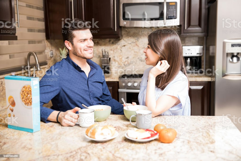 Lovely young couple having breakfast in kitchen stock photo