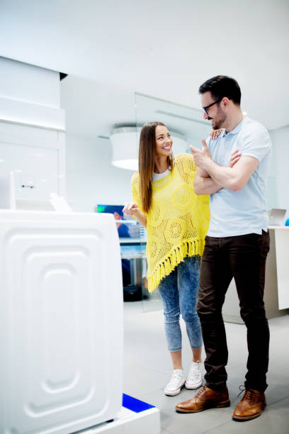 lovely young couple is searching for new household appliances in the electronics store. - happy person buy appliances stock photos and pictures