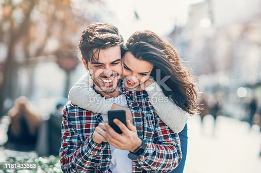 Young beautiful couple with mobile phone outdoors in the city