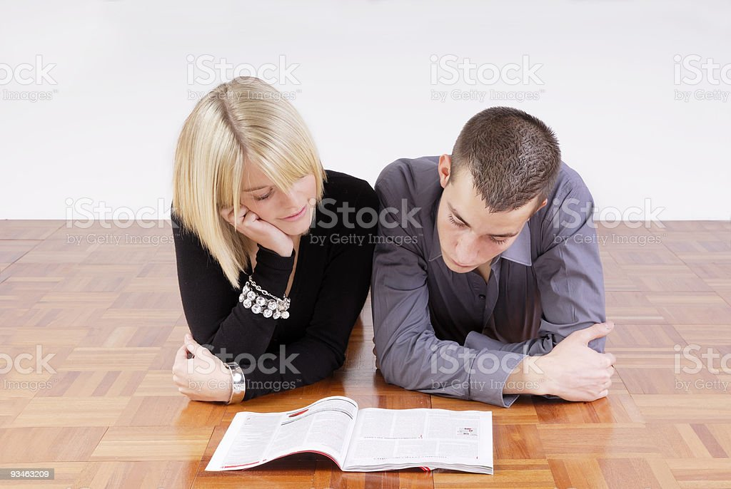 lovely young couple reading a magazine royalty-free stock photo