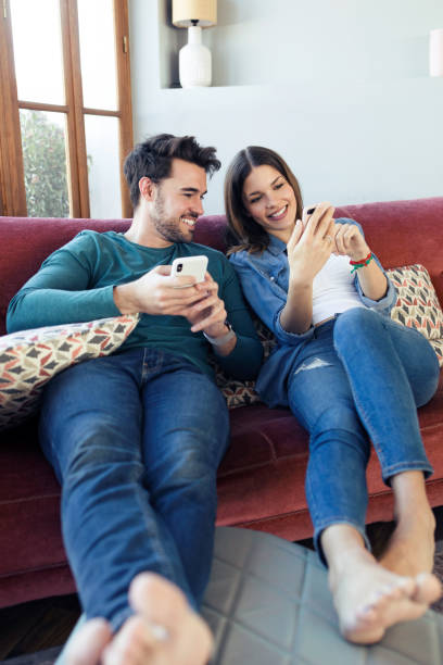 Lovely young couple using they mobile phone while sitting on sofa at home. stock photo