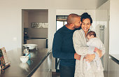 Man kissing his wife holding a newborn baby boy in kitchen. Lovely young family of three in morning in kitchen.