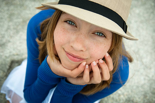 lovely young girl with a hat looking up on beach. - tween models stock photos and pictures