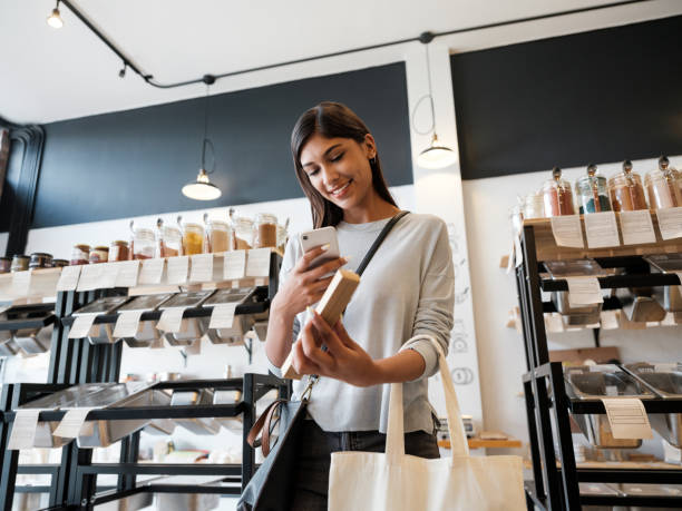 Lovely young latin woman taking photo of product in eco-friendly store stock photo