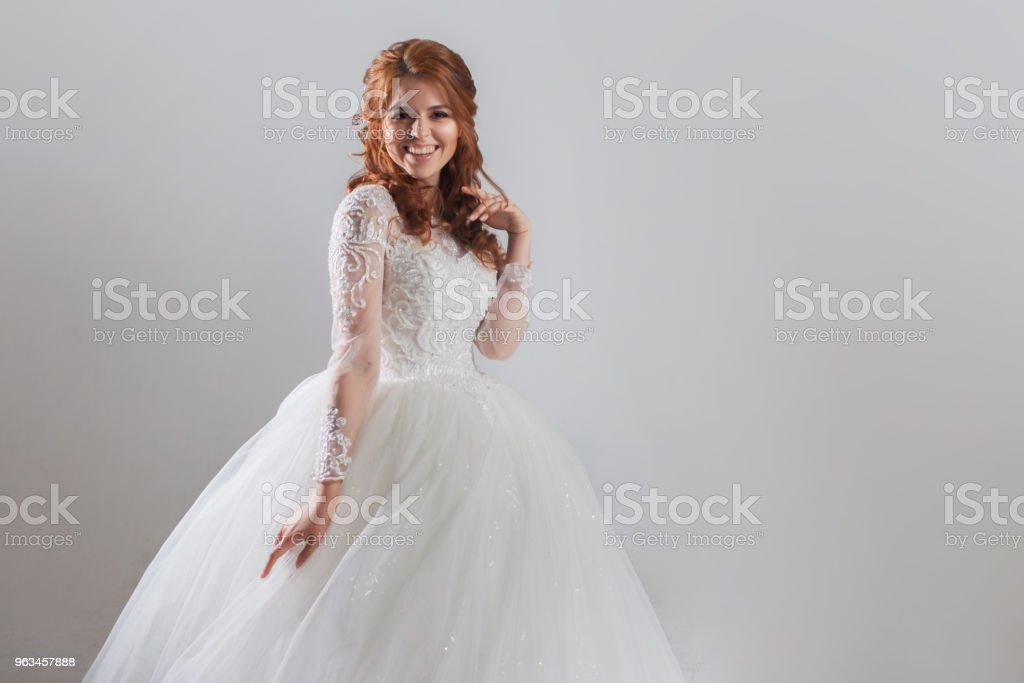 Lovely young woman bride in lavish wedding dress. Light background. - Zbiór zdjęć royalty-free (Ceremonia)
