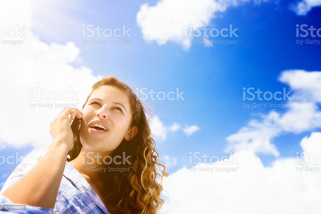Lovely young woman chats, smiling, on her cellphone in sunshine Lizenzfreies stock-foto