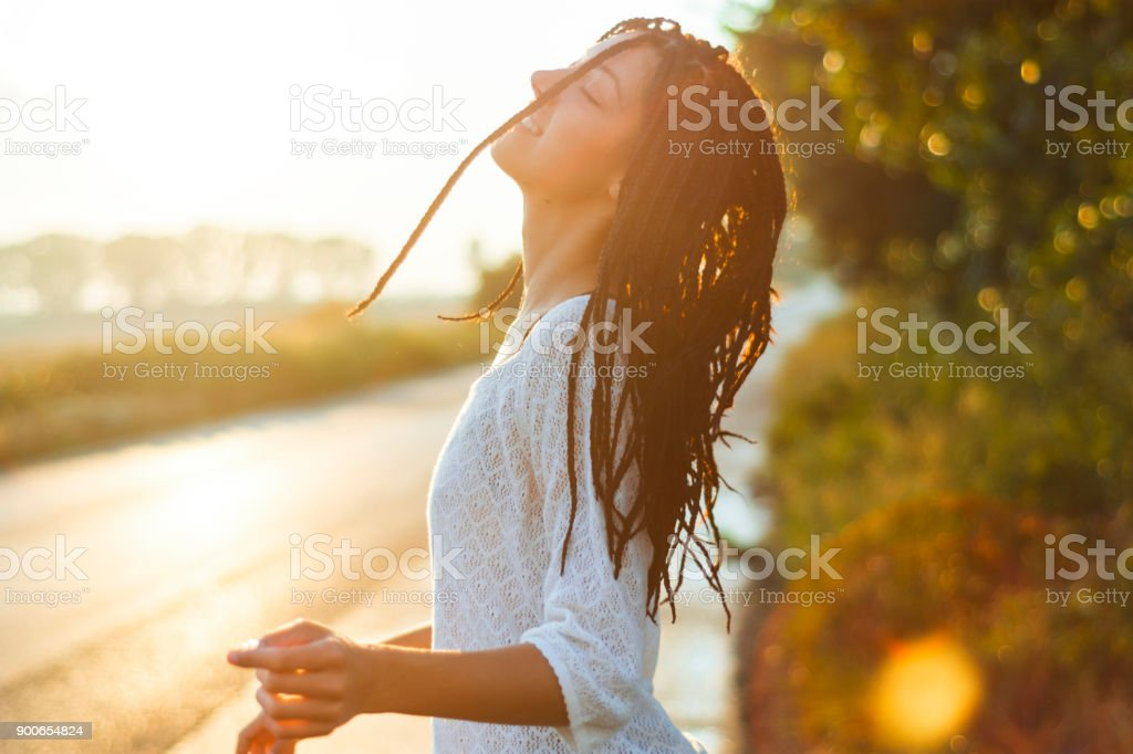 Lovely young woman enjoying the sunset stock photo
