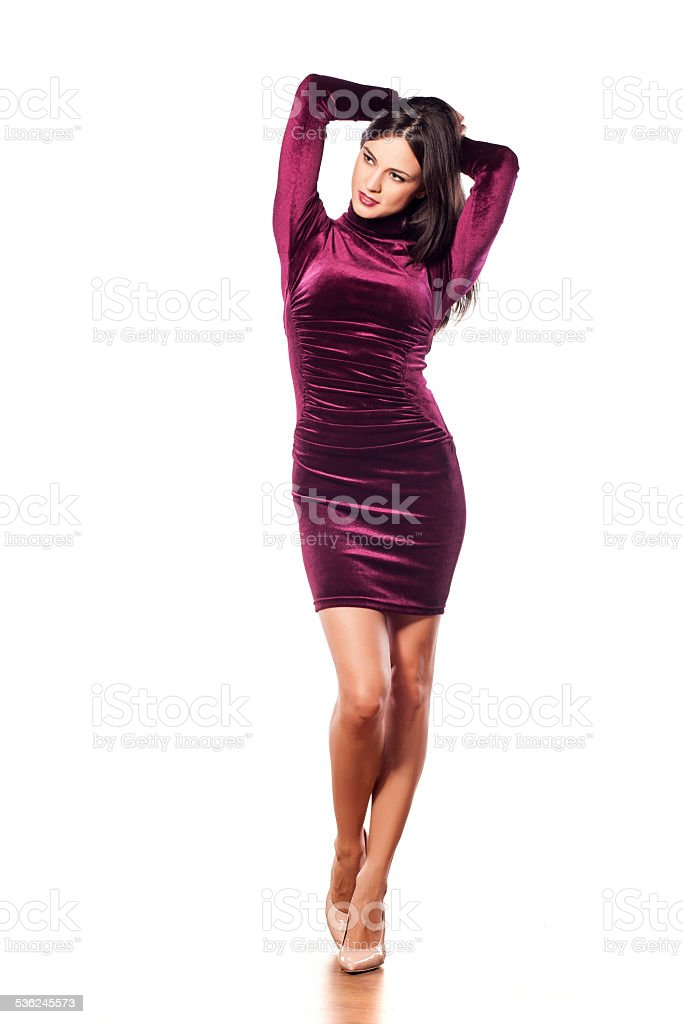 Lovely young woman in a tight purple dress stock photo