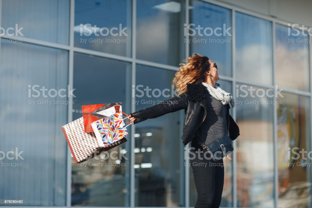 Lovely young woman turns around holding shopping bags on window background stock photo