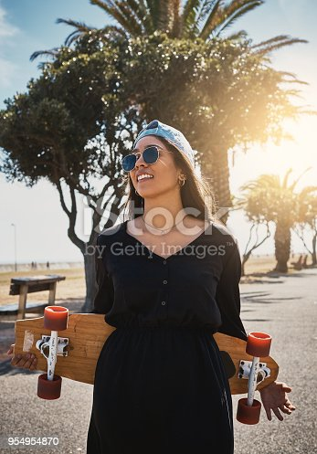 Young urban beauty holds her skateboard by the sea.