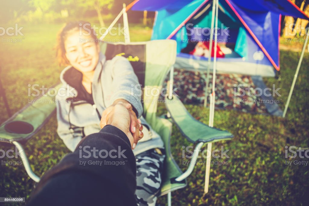 Lover women and men asians travel relax in the holiday. . camping on the Mountain. Shake hands lover sitting on a chair. Thailand stock photo
