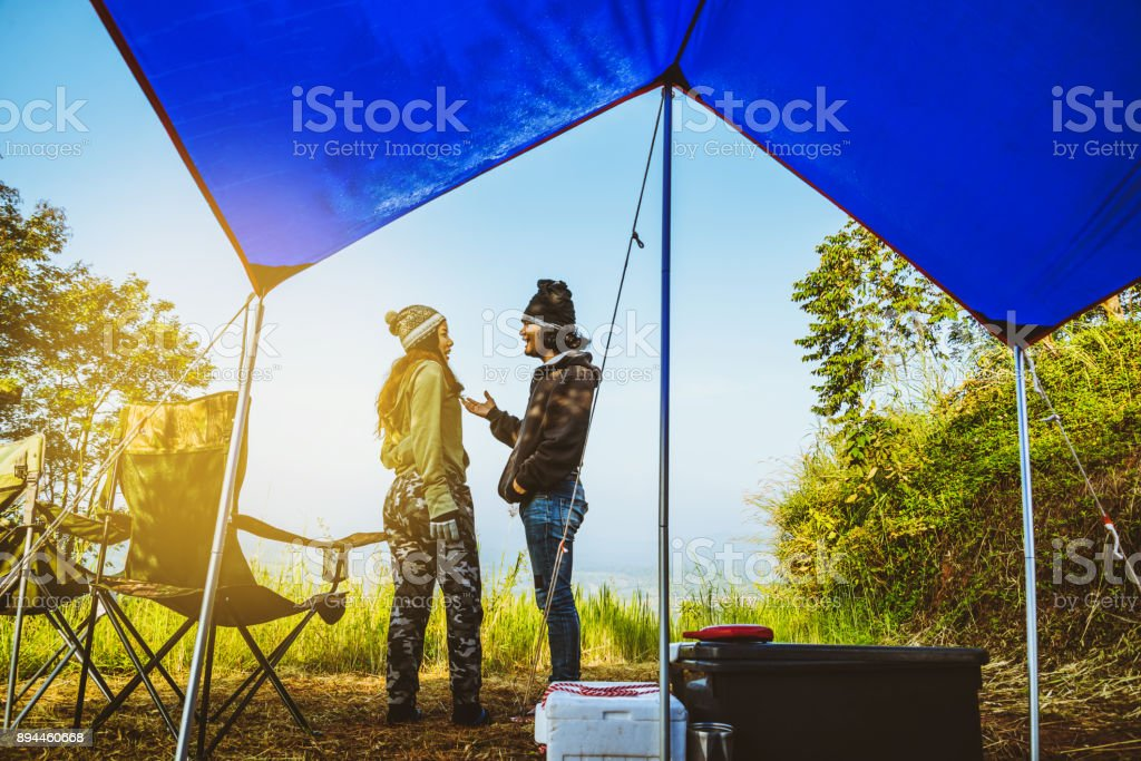 Lover women and men asians travel relax in the holiday. camping on the Mountain. Stand up look landscape on the mountain in the morning. Thailand stock photo