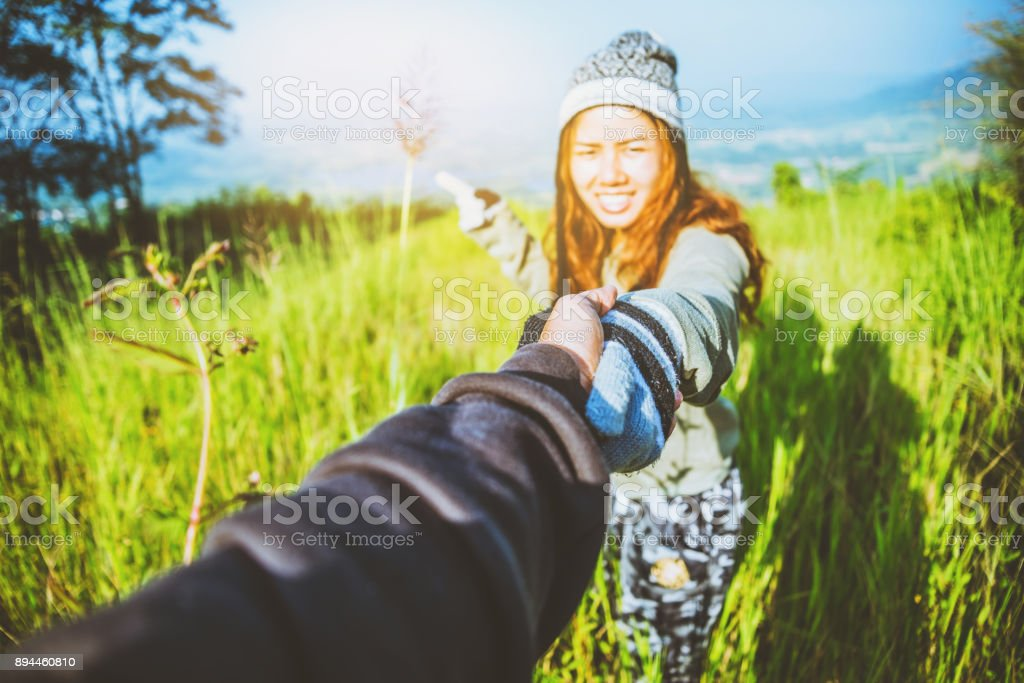 Lover women and men asians travel relax in the holiday. walk Shake hands green pasture on the Mountain. Thailand stock photo
