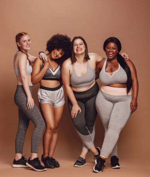 Lover your body Group of women of different race, figure type and size in sportswear standing together over brown background. Diverse women in sports clothing looking at camera and laughing. body positive stock pictures, royalty-free photos & images