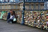 Paris, France - June 25, 2013: two lovers lock their padlock on Pont des Arts.