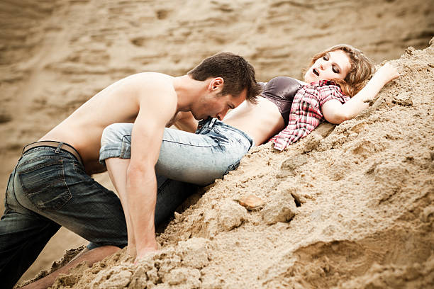 Lovers at sand Young couple outdoors portrait real couples making love stock pictures, royalty-free photos & images