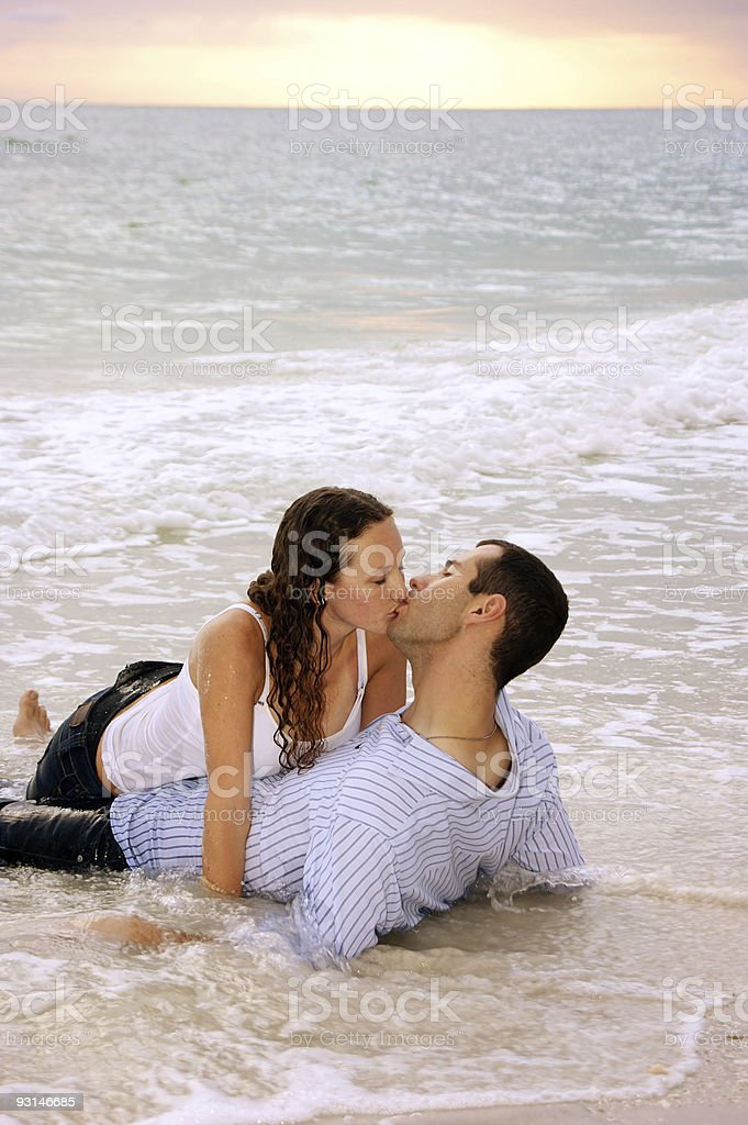 lovers being swept away with kiss and the tide stock photo