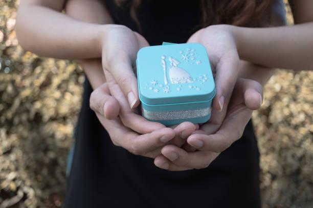liebenden paar holding blauen geschenkbox für hochzeitskonzept - hochzeitsbox stock-fotos und bilder