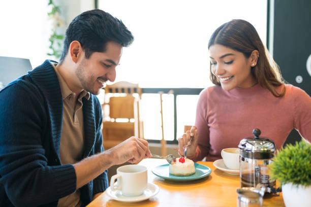 amantes disfrutando del postre juntos en el café - happy couple sharing a cup of coffee fotografías e imágenes de stock