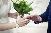 Lovers exchange rings. Close-up on a light background. The bride has a white watch on her arm.
