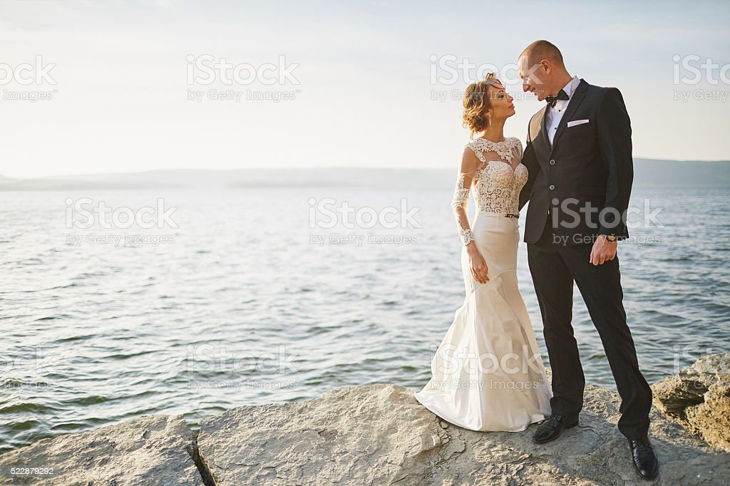 lovers in a wedding dress near the sea and mountains stock photo