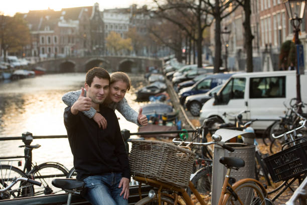 liebhaber in amsterdam bei sonnenuntergang - hochzeitsreise amsterdam stock-fotos und bilder