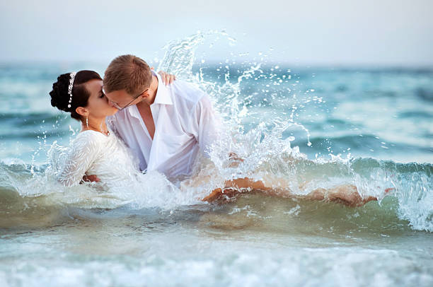 Lovers kissing in the waves stock photo