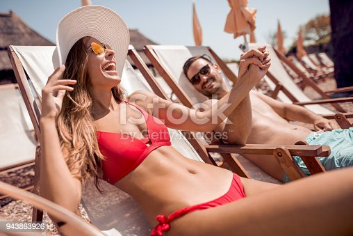 Love,travel,tourism,summer and people concept-smiling couple on vacation in swimwear sitting in chairs and sunbathing on beach.