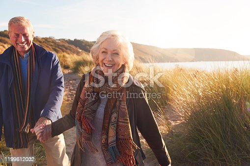 Loving Active Senior Couple Holding Hands As They Walk Through Sand Dunes