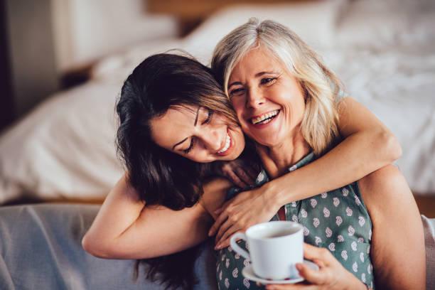 hija adulta abarca alegre senior madre cariñosa en casa - hija fotografías e imágenes de stock