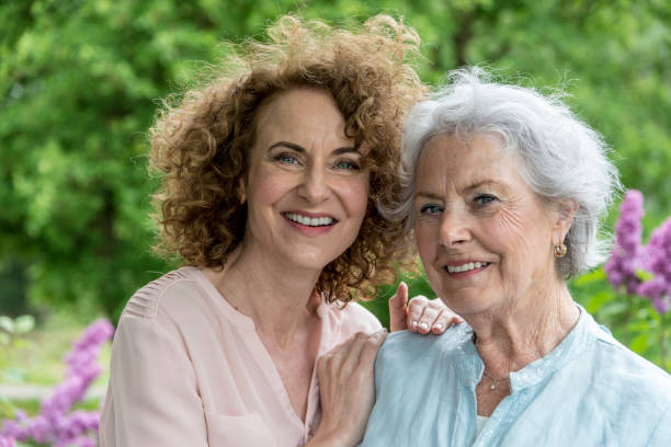 Loving adult daughter embracing cheerful senior mother at home stock photo